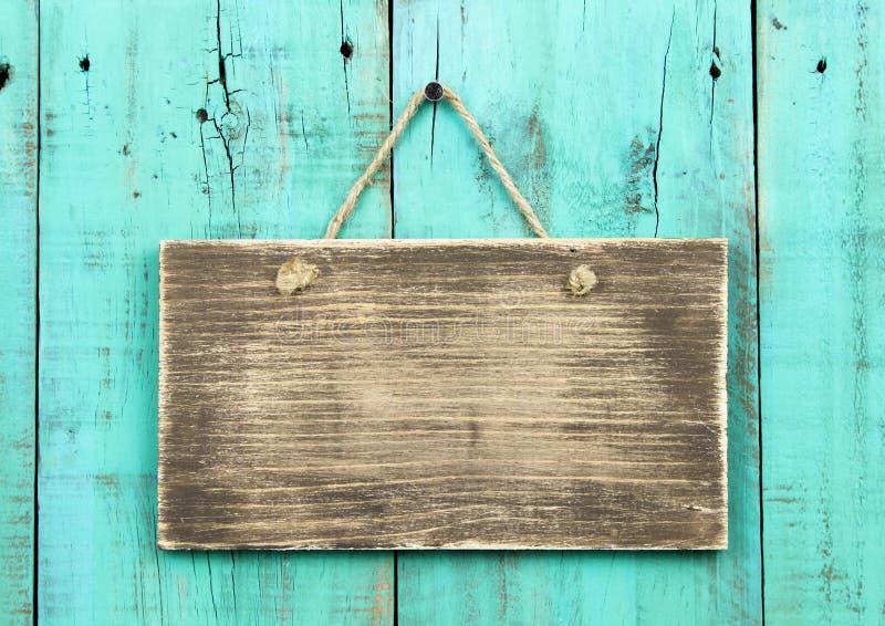 Segno di legno antico in bianco che appende sulla porta di legno afflitta di verde blu fotografie stock libere da diritti