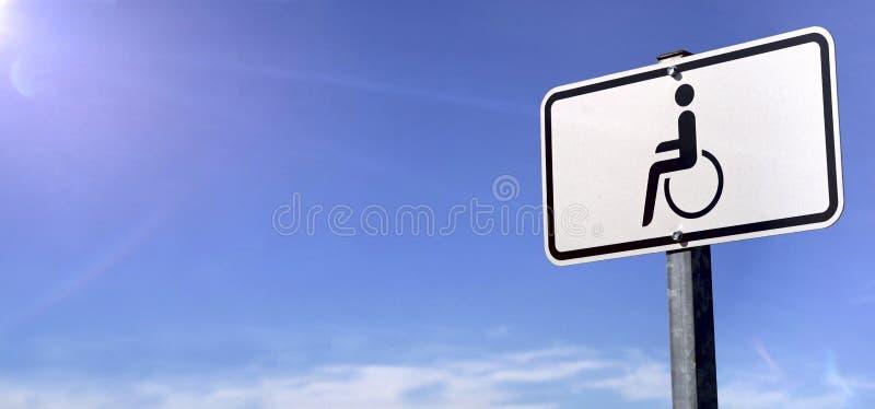 Segno di parcheggio di handicap davanti ad un cielo blu fotografie stock