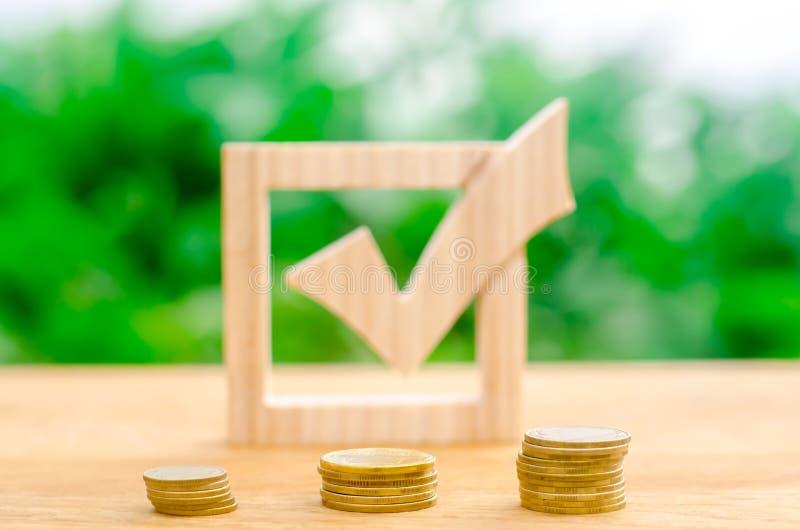 Segno di spunta e pile di legno di monete Tassi di interesse sui depositi e sui prestiti Incitamento dell'adozione dei regolament immagini stock libere da diritti