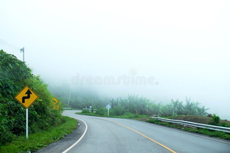 Segno di traffico stradale curvo sulla strada della montagna immagini stock