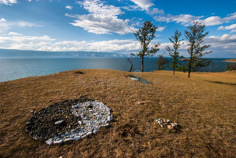 Segno di yin yang delle pietre colorate sulla riva del lago Baikal immagine stock libera da diritti