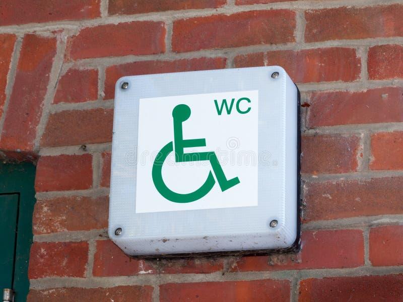 Segno disabile del gabinetto della toilette del wc fuori sulla fine del muro di mattoni immagini stock
