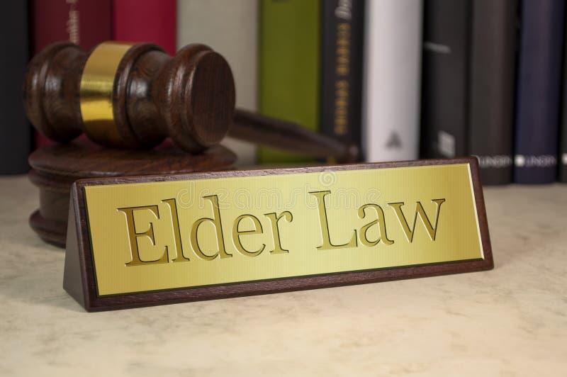 Segno dorato con legge dell'anziano e del martelletto fotografia stock