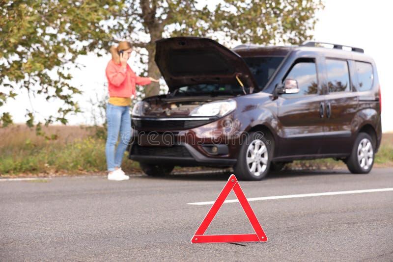 Segno e autista dell'arresto di emergenza vicino all'automobile rotta immagini stock libere da diritti