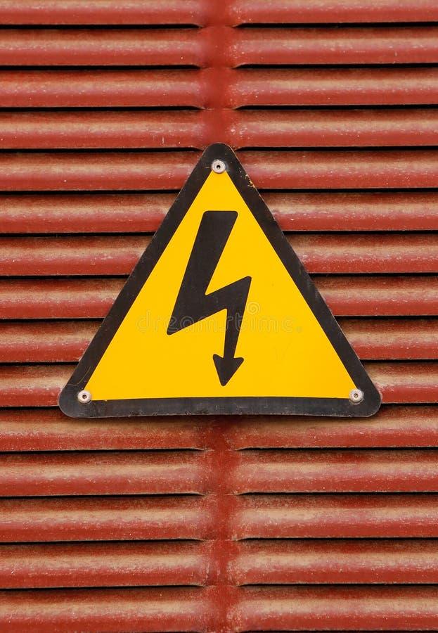 Segno elettrico dell'annuncio di rischio su un fondo rosso della parete del metallo immagine stock