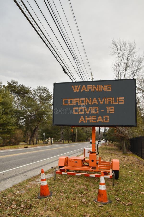 Segno elettronico digitale vicino a una piccola strada in una comunità che dice Warning coronavirus COVID - 19 in avanti immagini stock libere da diritti