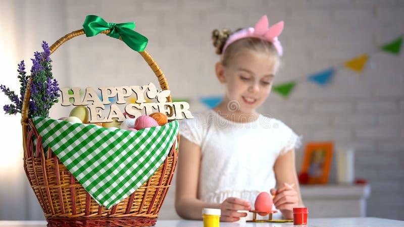 Segno felice di Pasqua sul canestro, uova sveglie della pittura della ragazza che si siedono alla tavola, festa immagini stock