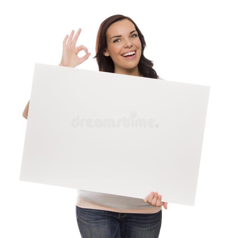 Segno femminile sorridente dello spazio in bianco della tenuta della corsa mista su bianco immagini stock libere da diritti