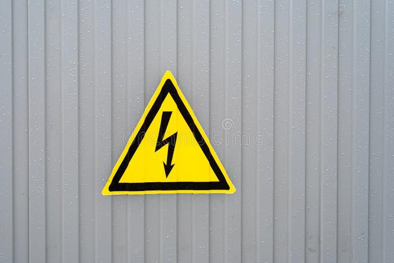 Segno giallo triangolare di tensione elettrica pericolosa sulla parete grigia raindrop fotografie stock libere da diritti