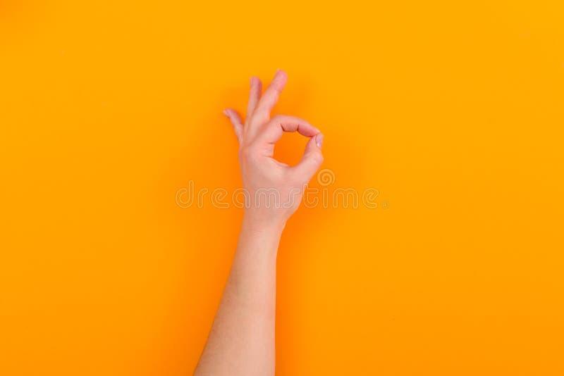 Segno GIUSTO di rappresentazione della giovane donna su fondo arancio fotografia stock libera da diritti