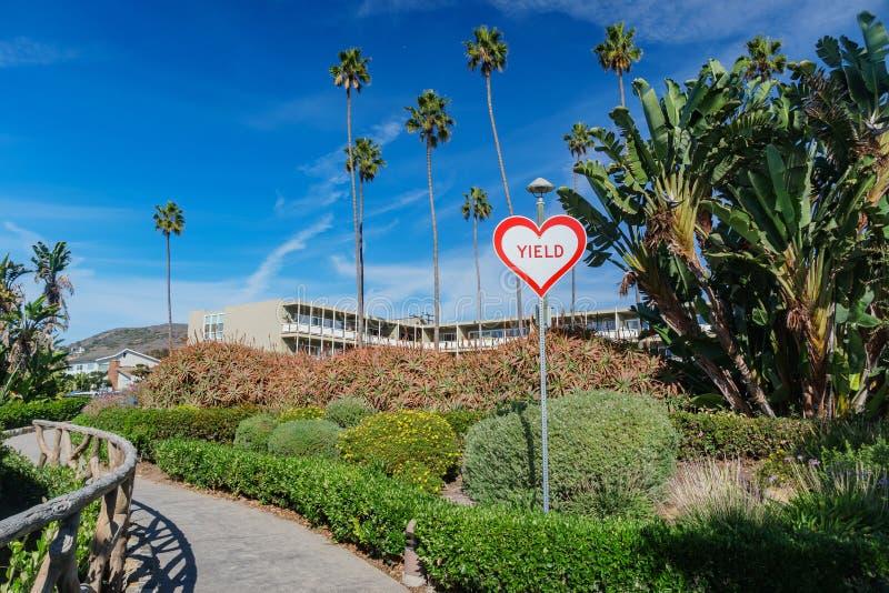 Segno interessante di forma del cuore con il testo del rendimento al Laguna Beach fotografia stock