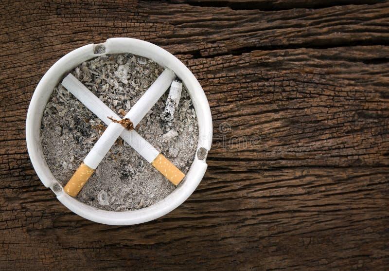 Segno non fumatori dalle sigarette in portacenere delle sigarette sui tum di legno immagini stock