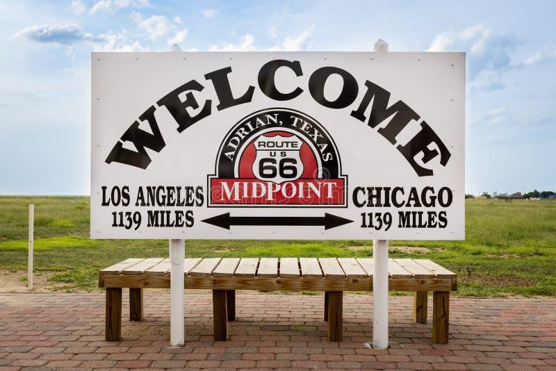 Segno positivo che segna il punto mediano fra Chicago e Los Angeles in Route 66 storico in Adrian, il Texas, U.S.A. immagine stock