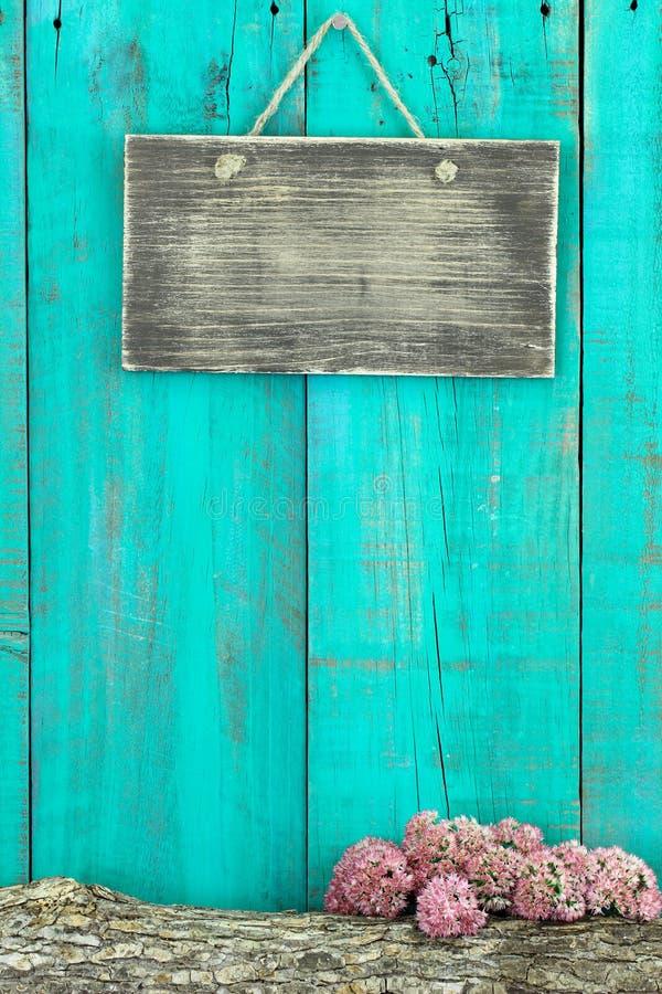 Segno rustico in bianco che appende sul recinto di legno blu dell'alzavola antica con il ceppo ed il confine rosa del fiore immagini stock libere da diritti
