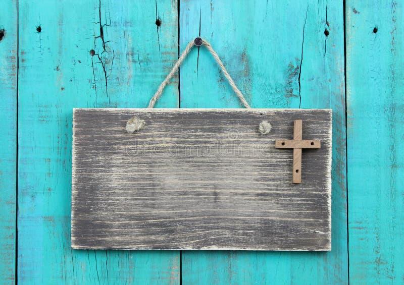 Segno stagionato in bianco con l'incrocio di legno che appende dalla corda sulla porta di legno blu dell'alzavola antica fotografia stock