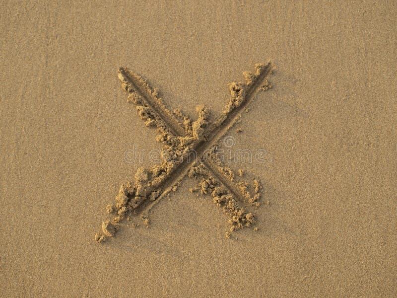 Segno trasversale dissipato sulla sabbia immagini stock