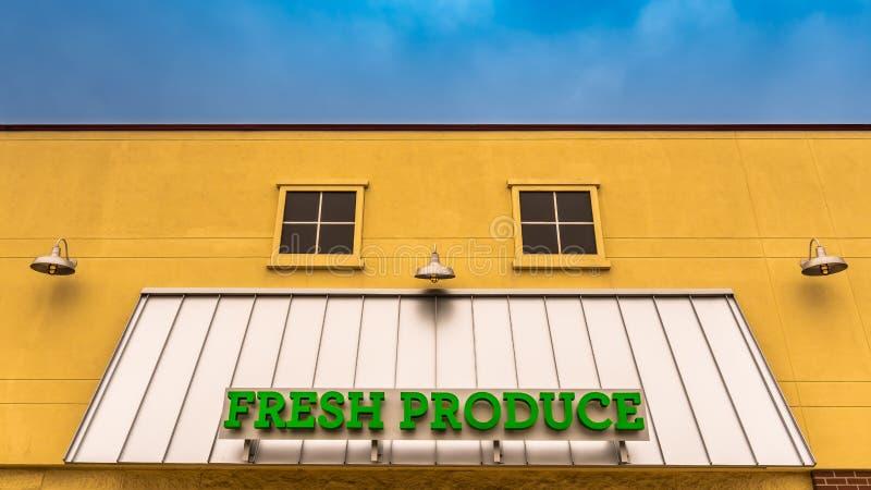 Segno verde intenso dei prodotti freschi su una parte anteriore gialla del deposito fotografia stock