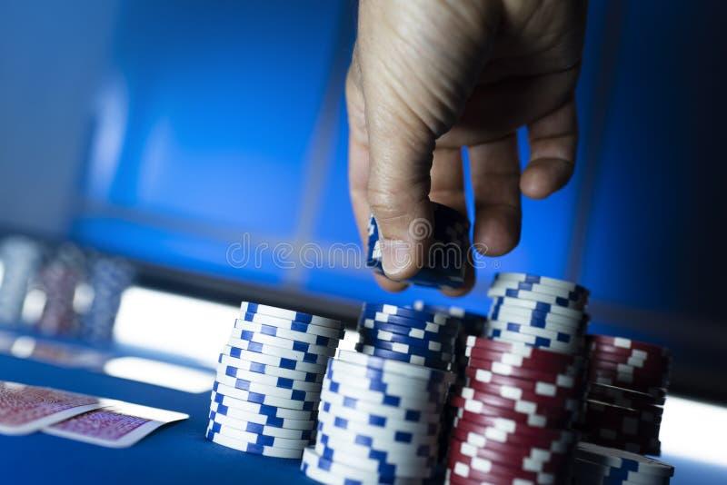 Segra mannen som staplar chiper på pokertabellen arkivbild