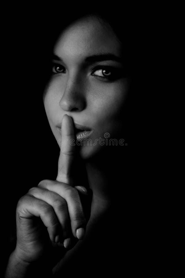 Segredo - mulher do mistério com o dedo nos bordos fotos de stock royalty free