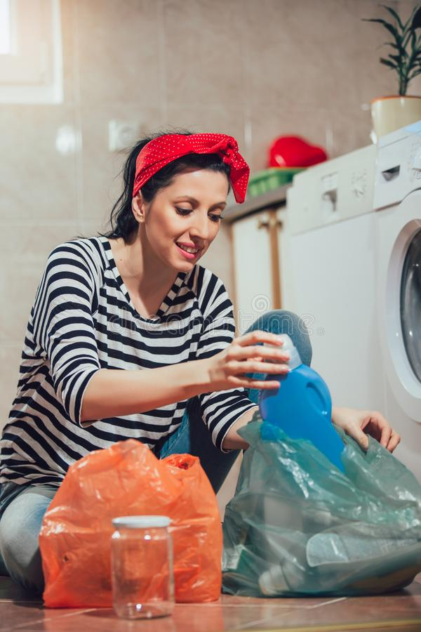 Segregating waste,a daily routine of smiling woman. Segregating waste,a daily routine of smiling young woman royalty free stock photography