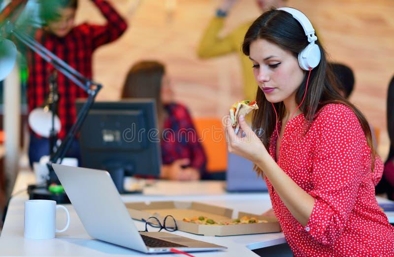 Segretaria allegra che gode della pizza all'ora di pranzo fotografia stock