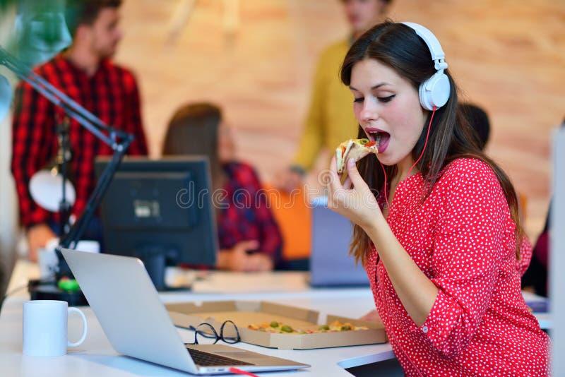 Segretaria allegra che gode della pizza all'ora di pranzo fotografie stock
