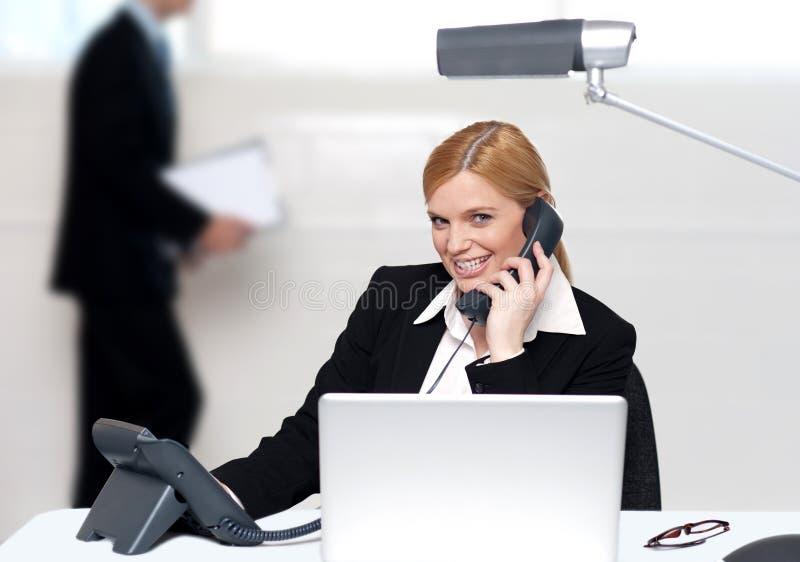 Segretaria attraente che assiste alla chiamata di telefono immagini stock