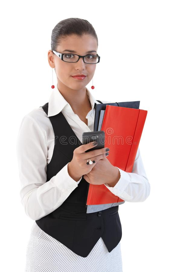 Segretaria attraente che per mezzo del telefono mobile fotografia stock libera da diritti