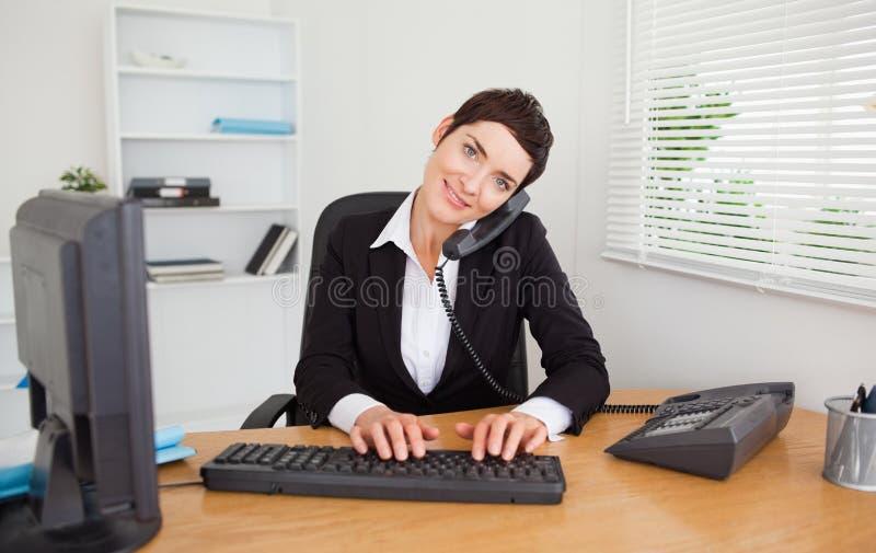 Segretaria professionista che risponde al telefono fotografia stock