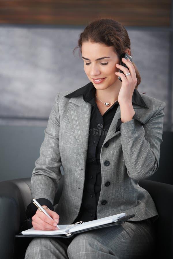 Segretaria sorridente sulle note di scrittura del telefono fotografia stock