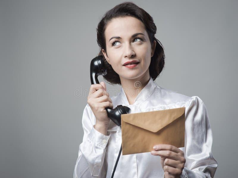 Segretario d'annata sul telefono con la busta fotografie stock libere da diritti