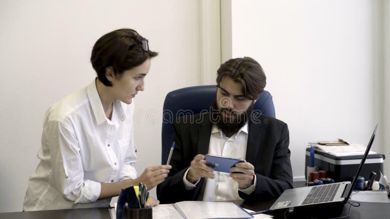 Segretario della donna mostra i documenti importanti al suo capo barbuto che è occupato con il gioco dei giochi dello Smart Phone immagine stock libera da diritti