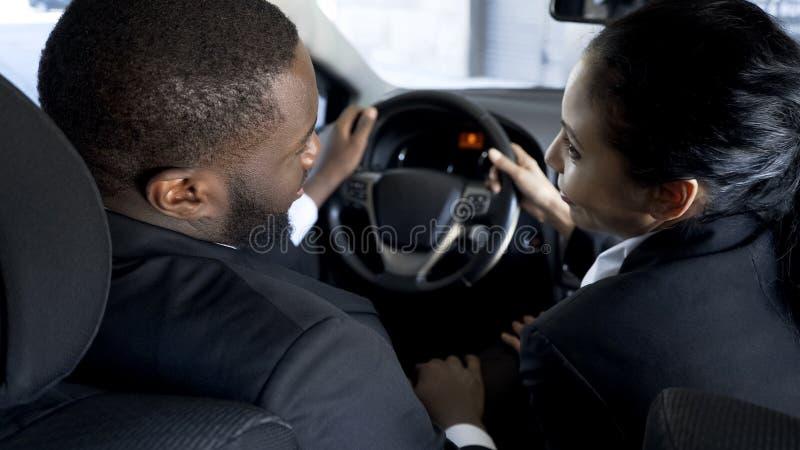 Segretario ingannevole attivamente che flirta con il capo in sua automobile per alzare la scala di carriera immagine stock