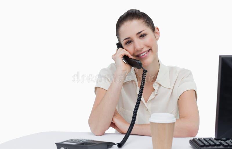 Segretario sorridente che risponde al telefono immagini stock