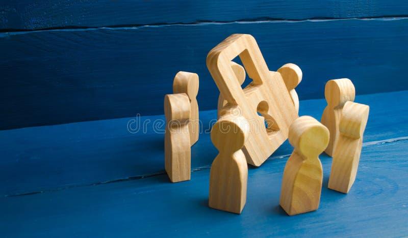 Segretezza della Banca, segreto medico Le figure di legno della gente stanno intorno ad un lucchetto su un fondo blu Il concetto  fotografia stock libera da diritti