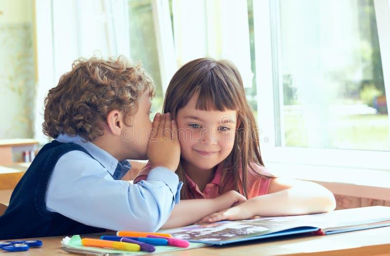 Segreti di sussurro del piccolo scolaro riccio durante la classe alla scuola elementare fotografia stock