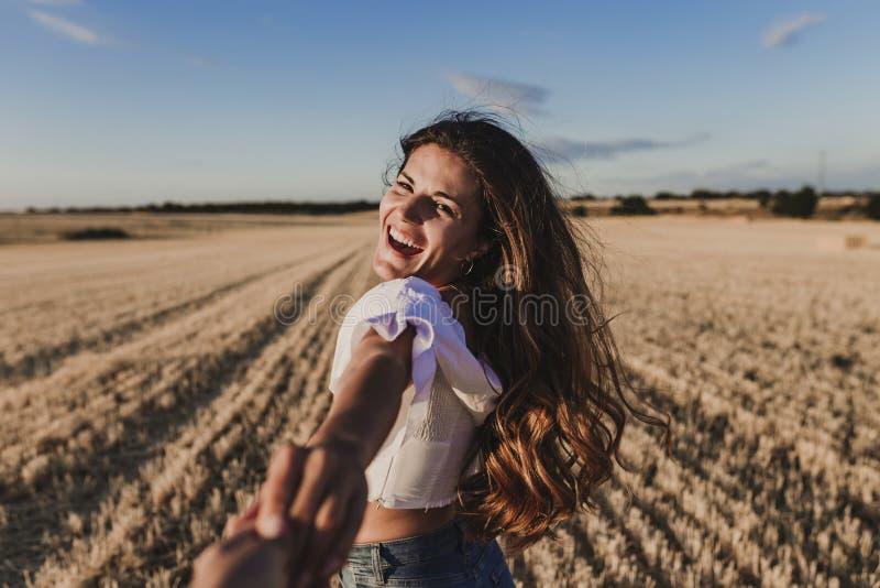 Seguami Mano della tenuta della giovane donna ed uomo principale al bello paesaggio di giallo tramonto della natura Vista dal lat fotografie stock libere da diritti
