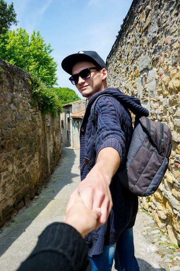 Seguami Un giovane tipo in un cappuccio conduce una ragazza dalla mano lungo la t fotografia stock