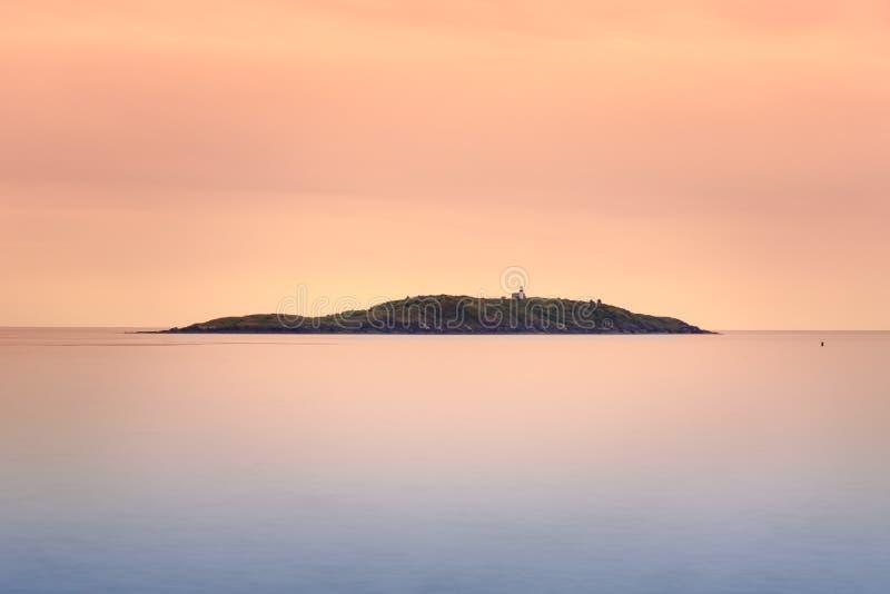 Seguin ö på solnedgången med det släta havet fotografering för bildbyråer