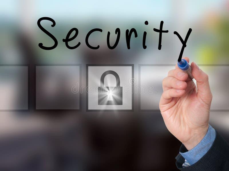 Segurança da escrita da mão do homem de negócios na placa transparente imagem de stock royalty free