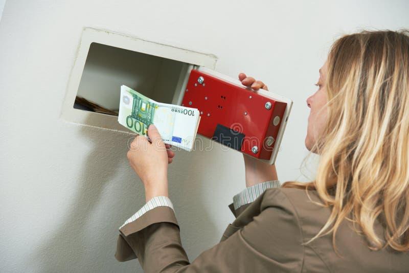 Segurança do dinheiro A mulher pôs o dinheiro das economias no cofre forte da parede fotografia de stock royalty free