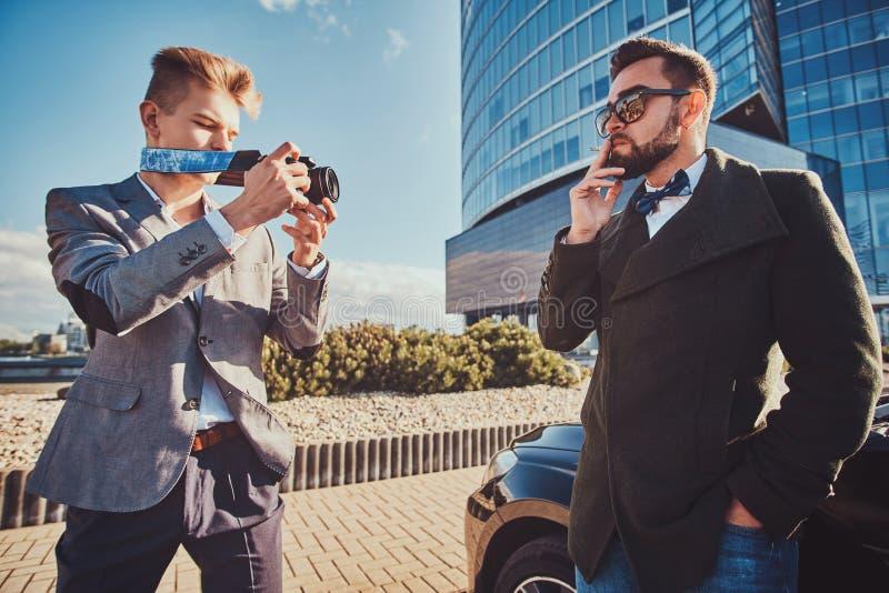 A segurança elegante está tomando a foto de seu chefe, que está fumando ao estar ao lado de seu carro fotos de stock royalty free