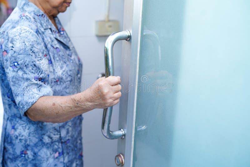 Seguran?a paciente asi?tica da porta do punho do banheiro do toalete do uso da mulher superior ou idosa da senhora idosa na divis fotografia de stock