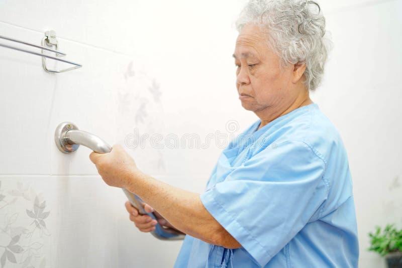 Seguran?a paciente asi?tica do punho do banheiro do toalete do uso da mulher superior ou idosa da senhora idosa na divis?o de hos fotografia de stock royalty free