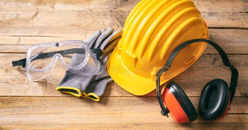 Seguridad de construcción Casco, auriculares, guantes y vidrios protectores en fondo de madera foto de archivo