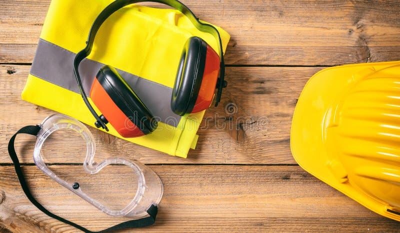 Seguridad de construcción Casco, auriculares y vidrios protectores en el fondo de madera, espacio de la copia, visión superior imágenes de archivo libres de regalías