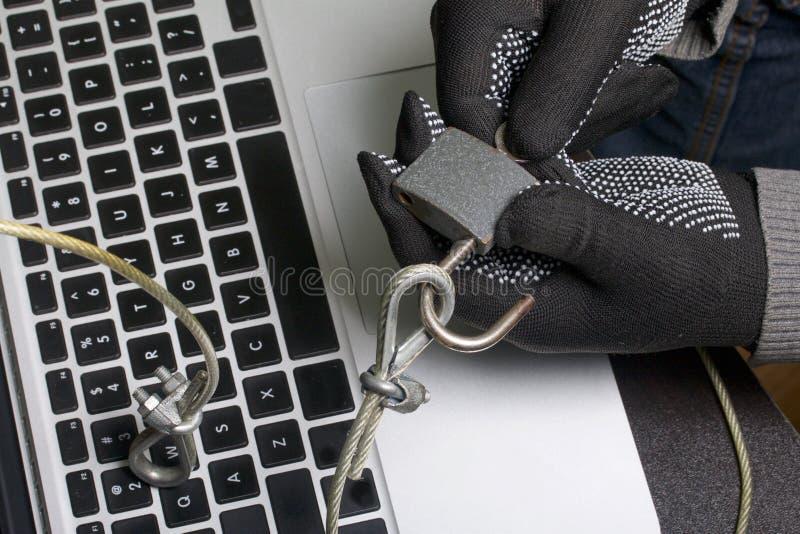 Seguridad de ordenador Protección del acceso a los datos El ordenador portátil es protegido por un cable de la seguridad y una ce fotografía de archivo libre de regalías