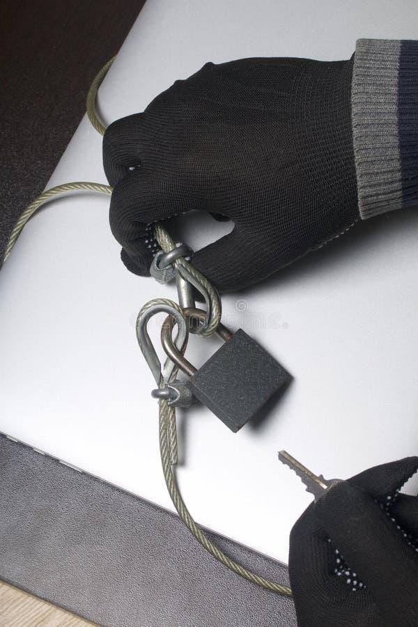 Seguridad de ordenador Protección del acceso a los datos El ordenador portátil es protegido por un cable de la seguridad y una ce foto de archivo libre de regalías