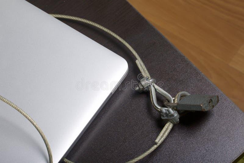 Seguridad de ordenador Protección del acceso a los datos El ordenador portátil es protegido por un cable de la seguridad y una ce fotografía de archivo