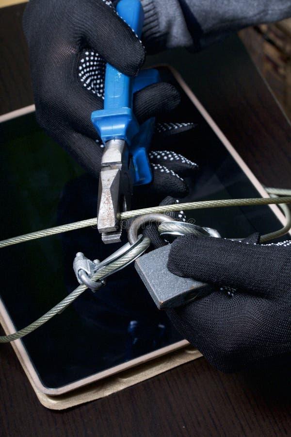 Seguridad de ordenador Protección del acceso a los datos La tableta es protegida por un cable de la seguridad y una cerradura Un  imagen de archivo libre de regalías